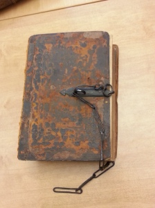 A very old book with a lock and chain used to fasten it in place to discourage theft.