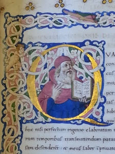 A close-up of an illuminated initial Q with a fat cherub to the left and a bearded elder smiling and holding a book in the center.