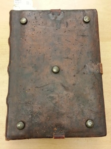 A very old rare book with leather cover with obvious holes from hungry bookworms.