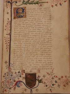 A page of an illuminated manuscript with a fancy decorated initial at top and a painting in the bottom margin.