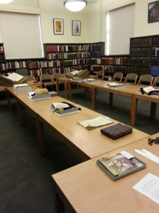 Two long tables in an academic reading room with medieval manuscripts displayed.