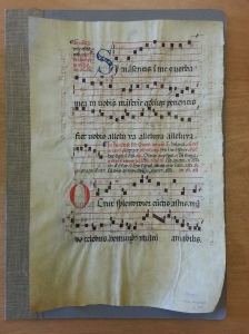 A music score from circa 1300 inscribed on animal hide; faint markings from a previous use are visible underneath.