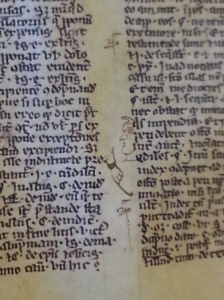 A close-up of a manuscript page that somebody/ies have doodled on; pictures include a staring face and a pointing hand.