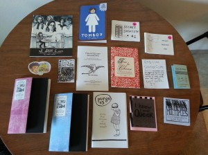 14 zines and 1 sticker spread out on a table.