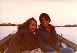 An elder woman with a head scarf seated next to a young woman with sunglasses on a small outrig motor boat.