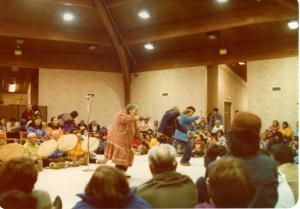 Inupiat people dancing with drummers seated behind them.