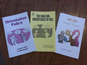 "Three comic-zines: one called Orientation Police with two smooching men being observed by a policeman who is saying ""Nope. Doesn't count. Not gay enough.""; one called The Amazing Adventures of Bill, with a man saying ""Hey Bill, what's new?"" and Bill responding ""I'm FAMOUS on the Internet!""; and one called Hot Men of the Monster Manual with four gay  monsters ogling a magazine centerfold."