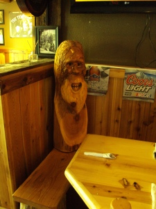 Image of a carved wooden Bigfoot head and shoulders, sitting on a bench at a restaurant bar table. The face has a wide smile and flowing beard.