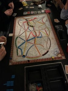 A game board covered with pieces, with several sets of hands around it, actively playing the game.