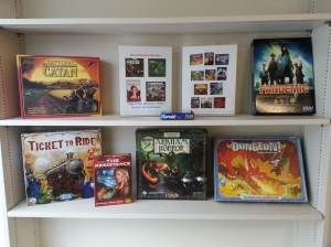 Several games and two informational posters on a wide bookshelf.