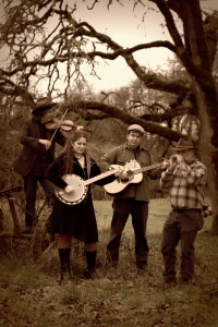 A sepia-toned photograph of members Chico Schwall, Kate Downing, Nathan Moore, and Dennis Soper standing in outside with their instruments.