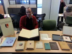 A table with women's suffrage materials, with a bespectacled person in a red cardigan.