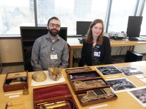 A person with glasses and a short beard and a person with long blond hair sit smiling in front of a table of medical oddities.