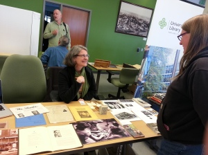 A person with a green scarf and black cardigan smiling and talking with a visitor across a table of photographs and other artifacts.