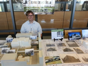 A smiling person with glasses sitting in front of a building model, blueprints, and photographs.