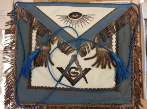 A ceremonial apron with fringe and Mason symbolism.