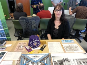 A person with glasses and a black cardigan sitting in front of a table with a purple fez, an ornate apron, and several paper documents.
