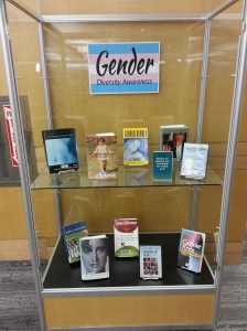 An open glass case with trans-relevant media and a sign reading Gender Diversity Awareness.