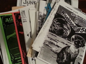 A fanned-out stack of zines from 1/4 page to full page size.