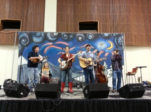 A band playing on a short stage with a large banner behind them. The banner is blue with stars and swirls.