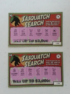 Two scratch tickets, described below. A bigfoot with red eyes hulks in the upper left corner.
