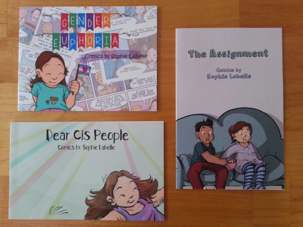 Three comic zines by Sophie LaBelle. Dear Cis People has a happy little girl rolling on the grass in the sunshine. Gender Euphoria has the same little girl waving a trans flag in front of overlapping comic strip images. The Assignment shows the little girl sitting on the couch with a little boy the same age, eating popcorn and staring to the left of the viewer, presumably at a television.