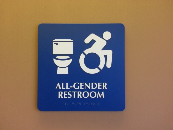 """Bright blue sign with white text and images. Text reads """"All Gender Restroom"""" and images show a toilet and an accessibility icon. There is braille at the bottom."""