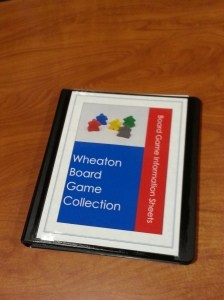 "A binder with a brightly colored cover. Text reads ""Wheaton Board Game Collection"" and ""Board Game Information Sheets."" There is also an image of several colorful meeples."