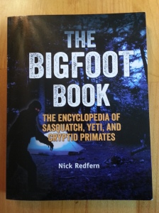 A dark, glossy book cover with a glowing-eyed bigfoot by a tent outdoors.