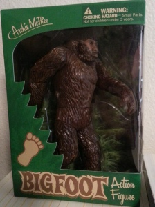 A brown plastic bigfoot with articulated elbows, shoulders, waist, and legs. Item is in a green box with clear plastic to view.