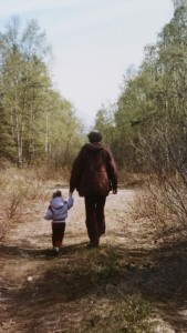 A toddler and man holding hands and walking down a sparse forest path, taken from behind.