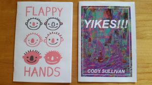 "Two zines, one titled ""Flappy Hands"" with illustrations of six smiling facing; the other titled ""Yikes!!!"" with bright glitch art."