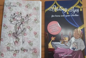 "On the left, a chapbook with a flowery cover with the title ""Volume 1: Bless my hairy butt."" There is an image of a group of women braiding each others' butt hair. On the right, a zine with the text ""Dating Tips for trans and queer weirdos."" There is an image of a smiling young person standing in front of a fancy table."