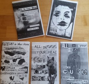 Five grayscale zines spread out on a table.