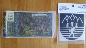 "On the left, a clipping of a ""Bizarro"" cartoon by Dan Piraro. Text reads ""Bigfoot returns home for a family reunion."" Several hairy hominids are gathered, each with a different part of the body enlarged. One of them is remarking ""Well, if it isn't Mr. Famous."" On the right, a bumper sticker of the classic striding Patty below a simple line drawing of trees and mountains."