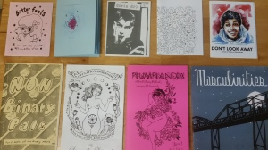 Nine colorful zines on a table.