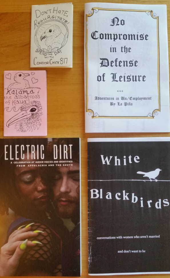 Electric Dirt, a half page size zine with a photograph of two queers embracing; White Blackbirds, a half page size zine with a picture of a white blackbird on a line; No Compromise in the Defense of Leisure, a half page size zine with Gothic lettering; Don't Hate, Regurgitate, a mini folding zine with a picture of a baby condor; and Kalama & the Albatross of Kaua'i, a mini folding zine with a picture of a baby albatross with an adult albatross.