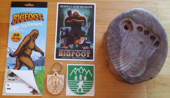 "Five objects on a table: Bigfoot gift tag stickers from Archie McPhee, with a classic frame 352 pose illustration; postcard with an illustration of Bigfoot with crossed arms surrounded by various small and large wildlife, with text reading ""Respect Our Wildlife. This forest is protected by Bigfoot. Pacific Northwest""; a small die-cut wooden keychain with frame 352 image with trees and mountains; the same image in green as a sticker; and a large oval wood block with a bigfoot footprint cut out on the top, with a deep hole in the big toe for a pencil."