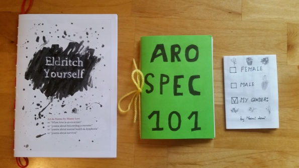 "Three zines on a table. On the left, a half-size zine titled ""Eldritch Yourself"" with ink blotches and red yarn binding. In the middle, a quarter-size zine titled AROSPEC 101 on green paper with yellow yarn binding. On the right, a one-page-folded zine titled ""My Gender"" with three ticky boxes for ""Female"", ""Male"", and ""My Gender""."