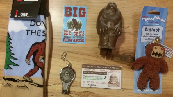 "A pair of socks with a conifer and Bigfoot in profile with text reading ""Don't Sass the Squatch""; a loyalty card with Bigfoot in profile; a drivers license with a close-up of Bigfoot's face; nail clippers with Bigfoot's face surrounded by footprints; a brown plastic Bigfoot; and a Bigfoot doll made of brown string and beads."