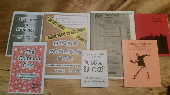 Seven colorful zines of various sizes spread on a wooden table.